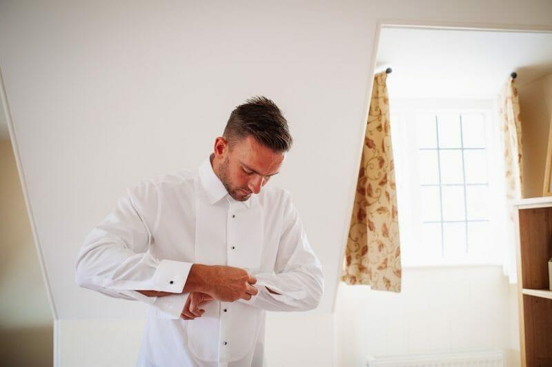 groom putting shirt on