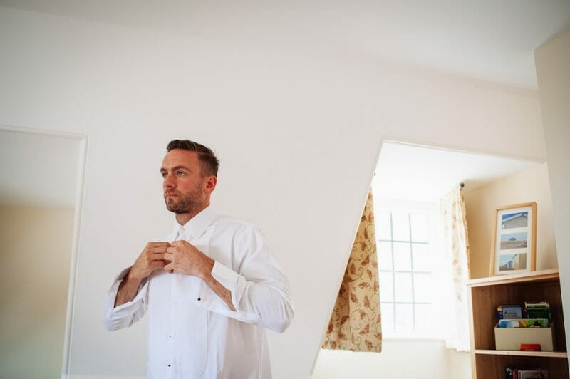 groom buttoning up shirt
