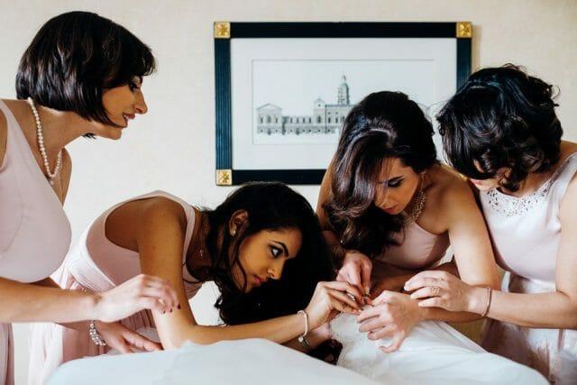 bridesmaids fixing the dress