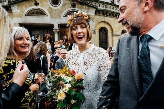 a bride with a bob haircut and autumnal orange flower crown and wildflower bouquet